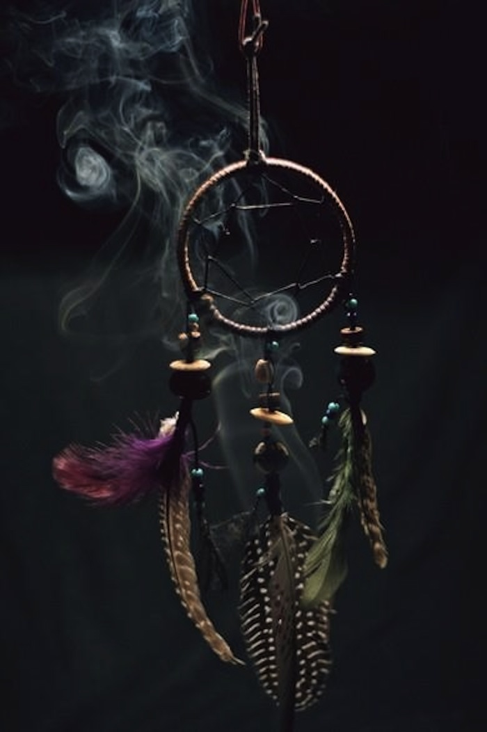 Dream catcher with sage smoke to illustrate article on smudging. Read more at TheNuminous.net!