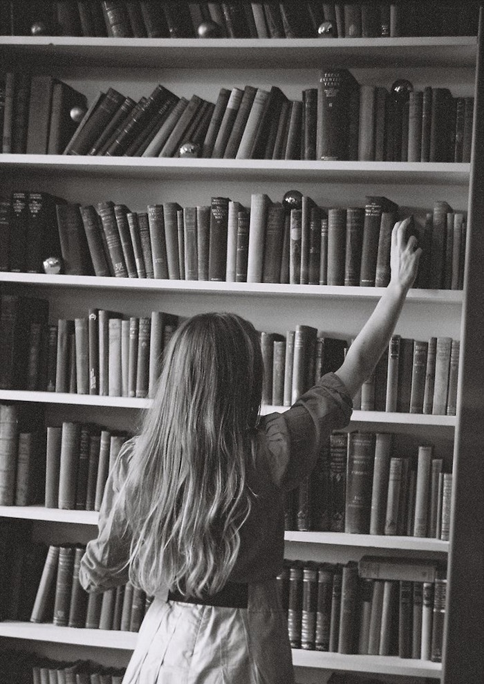 Black and white shot of a girl reaching for a book in a library featured on TheNuminous.net
